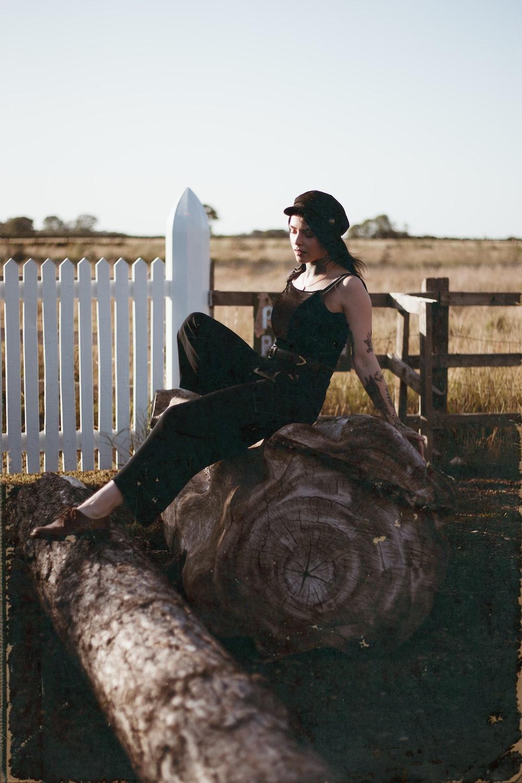 sitting woman wearing black sleeveless top