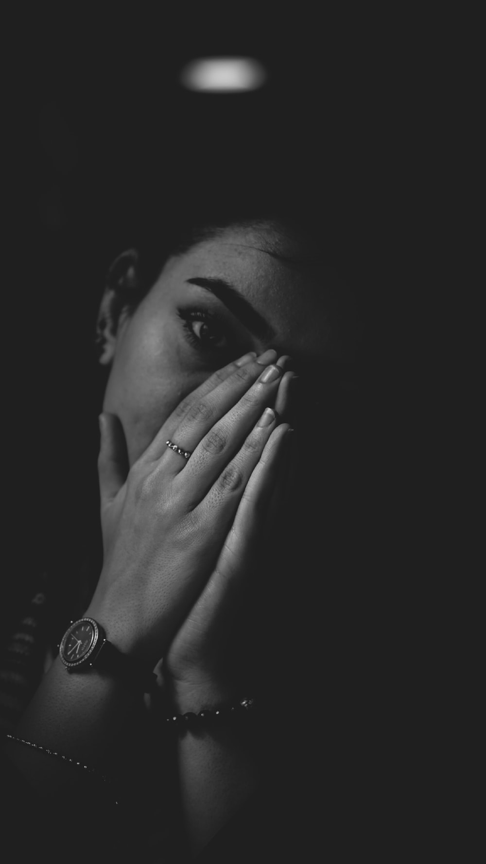 grayscale photography of woman covering her nose wit hands