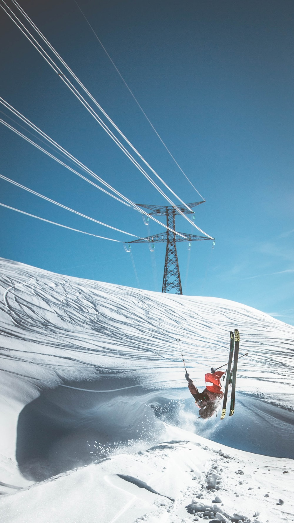 man skiing on snow near electric tower