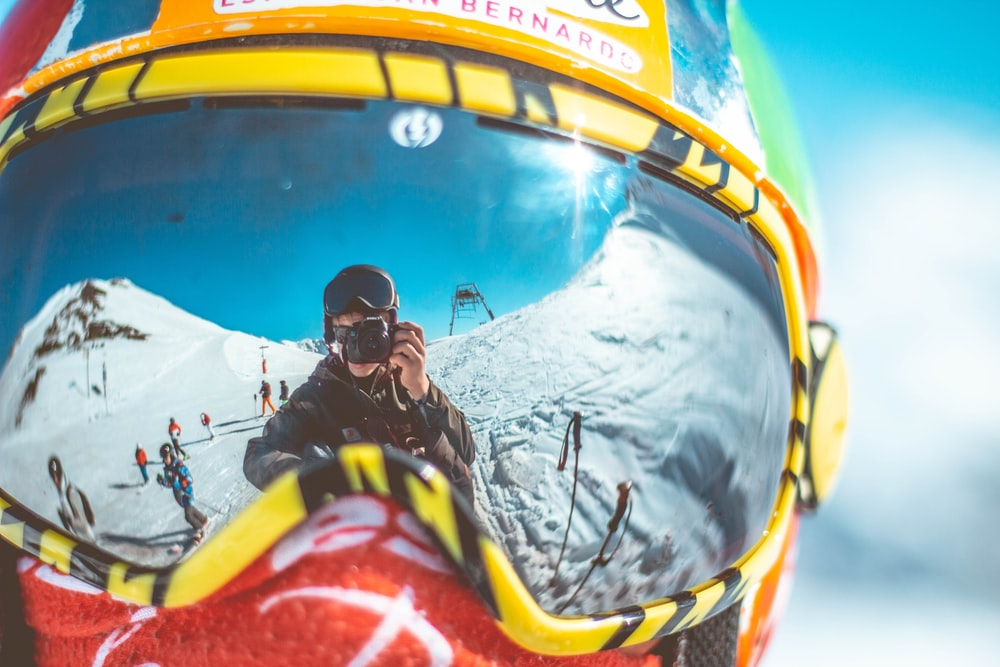 reflection of man holding camera on person's goggles