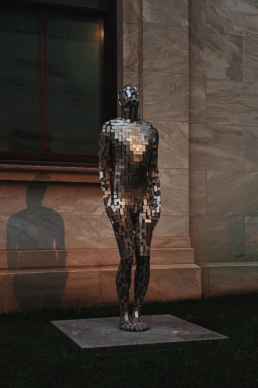 man's statue beside building