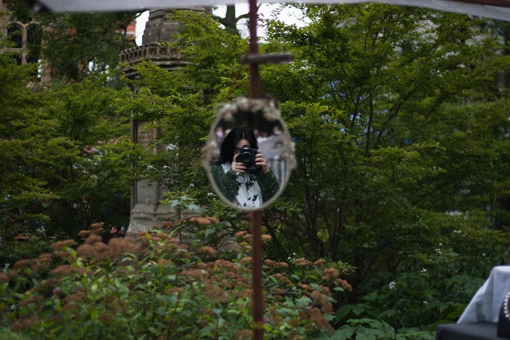 woman taking photo of mirror during daytime