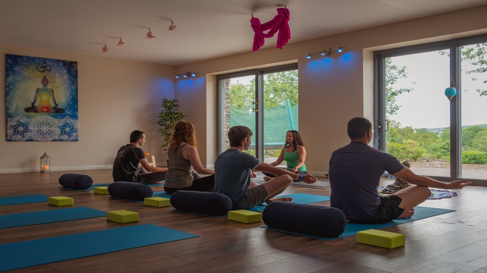 five persons doing yoga inside room
