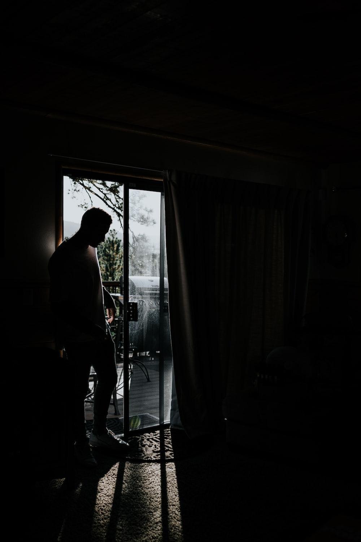 man standing beside glass sliding door