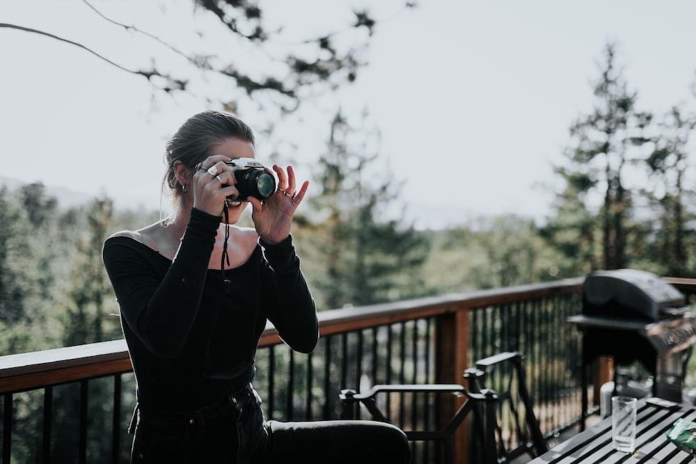 woman sitting beside balustrade taking photo