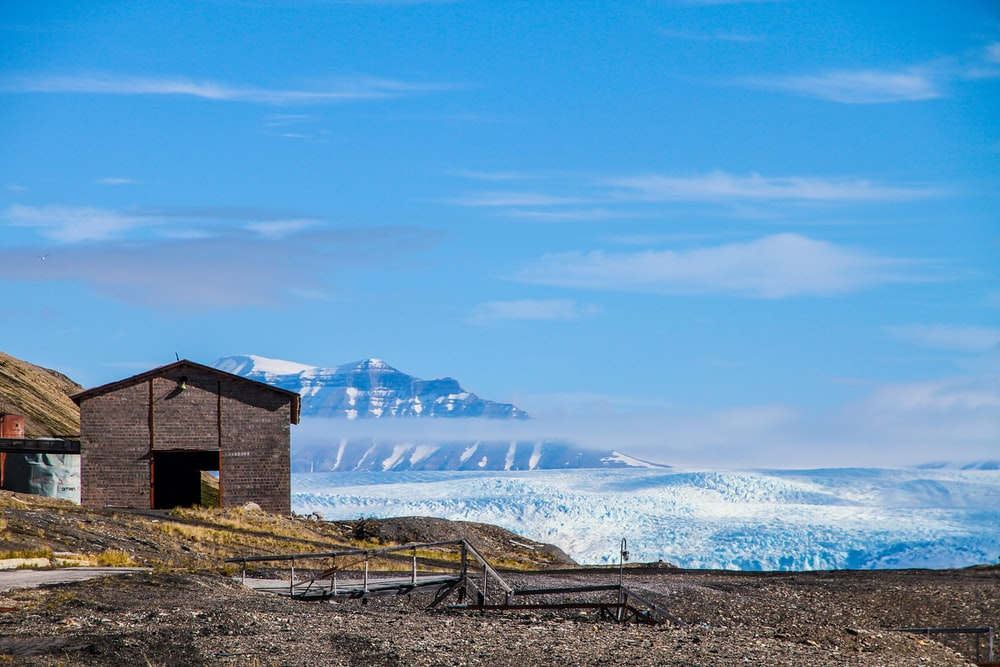 gray wooden shed overlooking snow-capped mountain