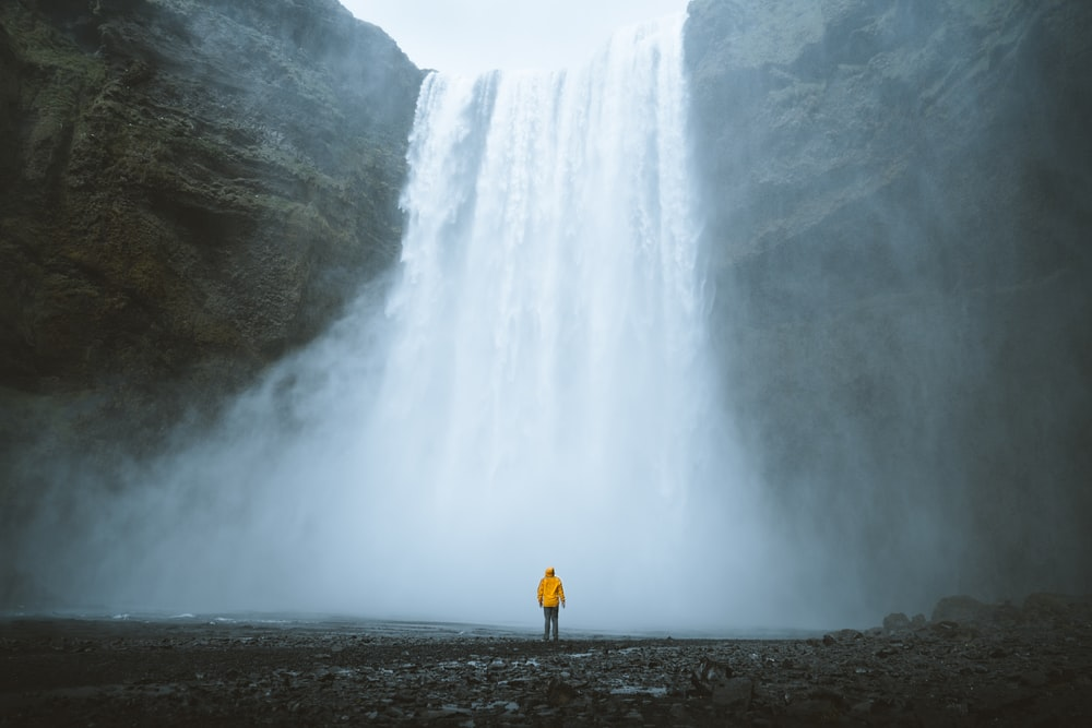 person standing near waterfalls