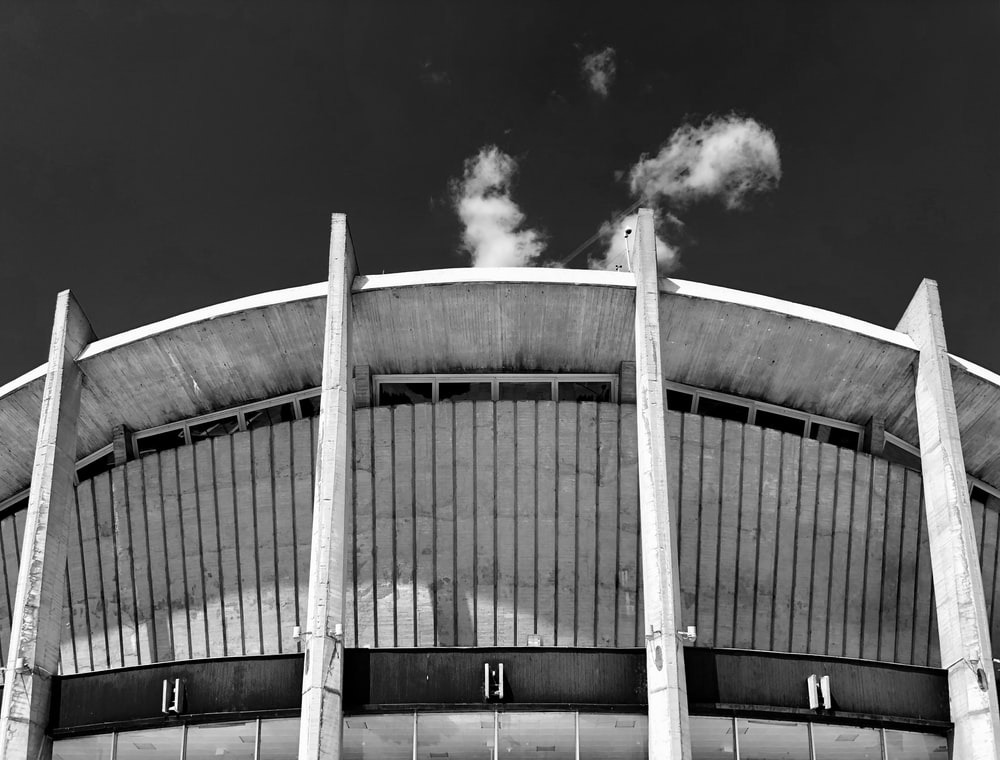 grayscale photo of stadium under clear sky
