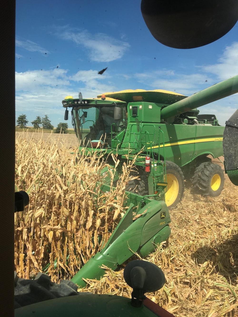 green harvester harvesting corn in field