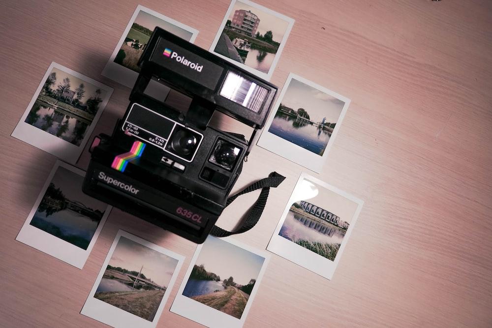 assorted photos surrounding Polaroid camera on table