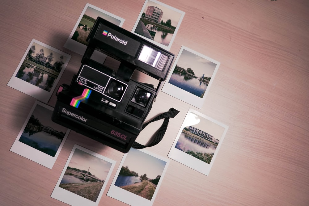 assorted photos surrounding Polaroid camera on table