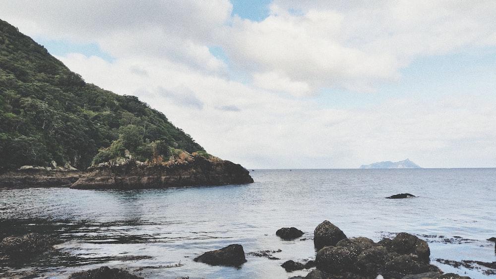 rocks on shore near hill