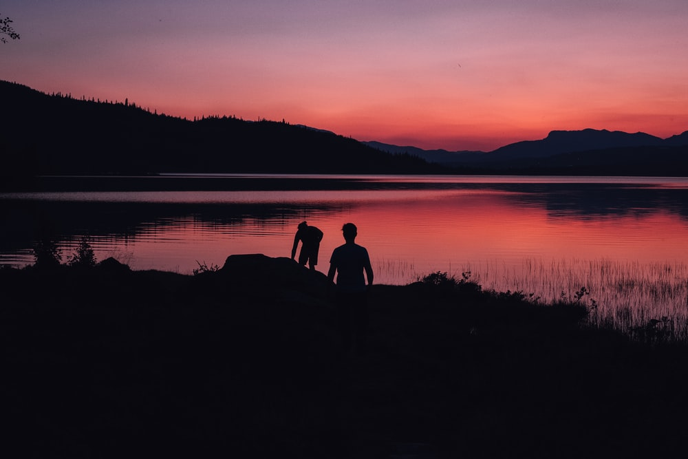 silhouette of two people standing near body of water under orange sky