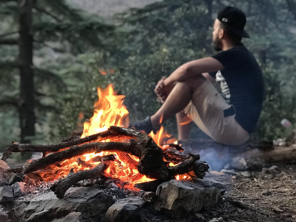 man sitting beside bonfire