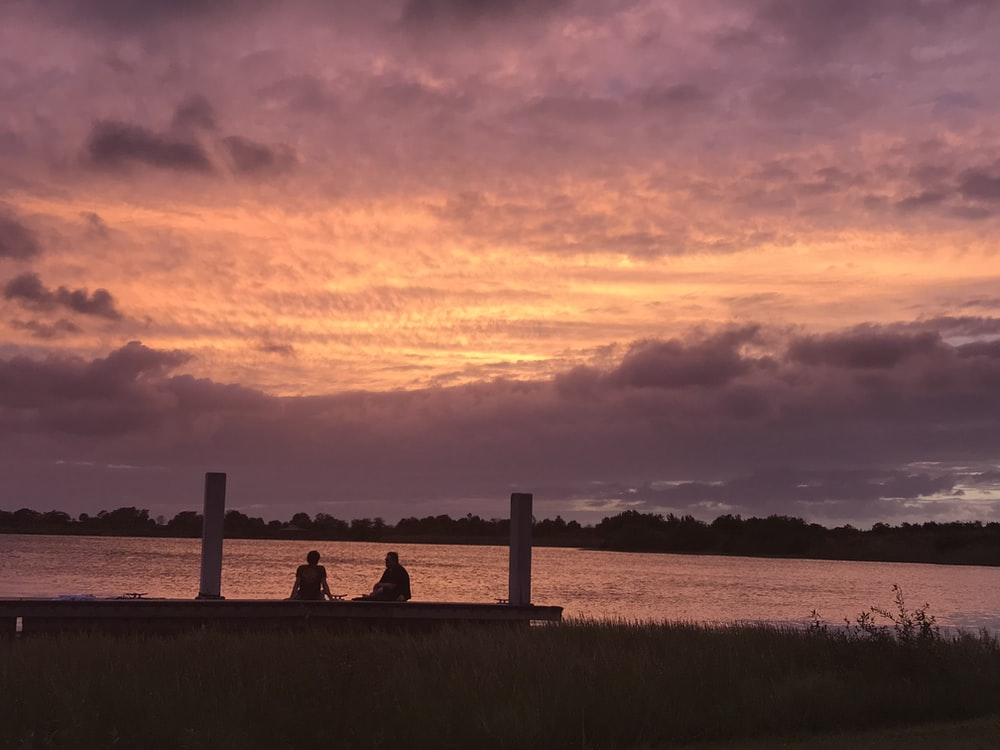 two people sitting near body of water