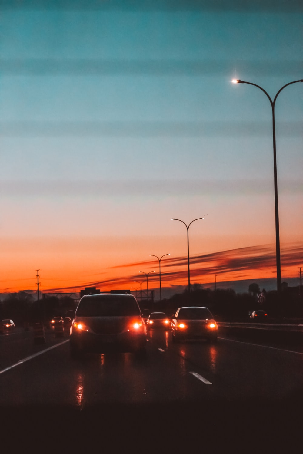 vehicles crossing on road during sunset