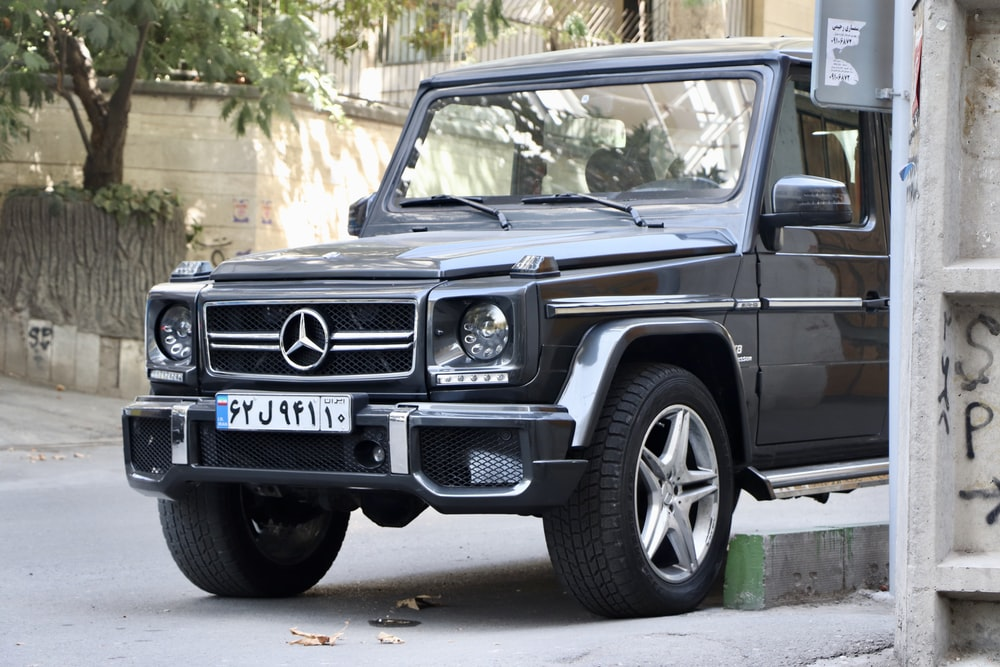 black Mercedes-Benz vehicle parked beside wall