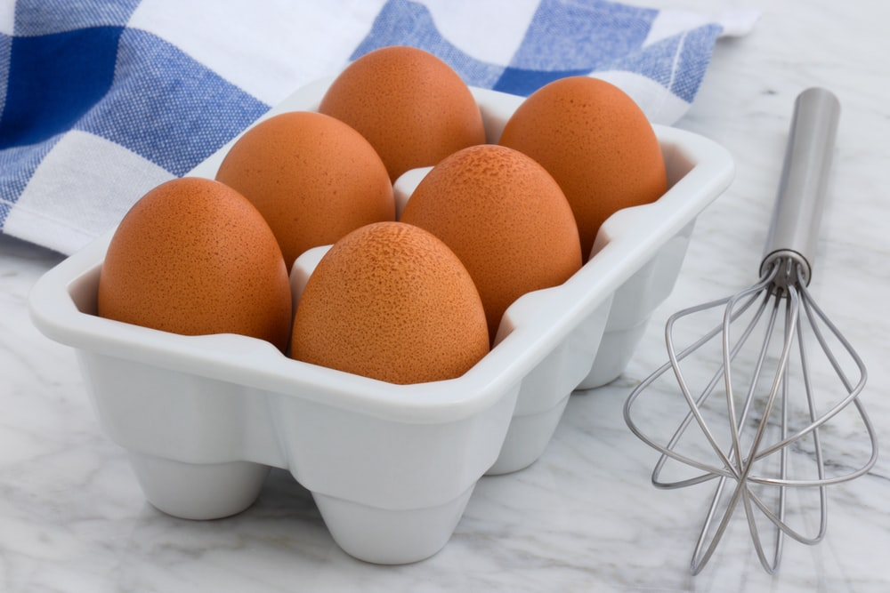 six brown eggs in tray