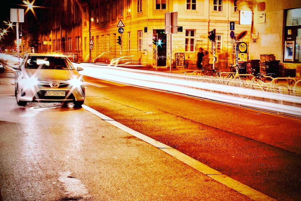 white sedan on asphalt road
