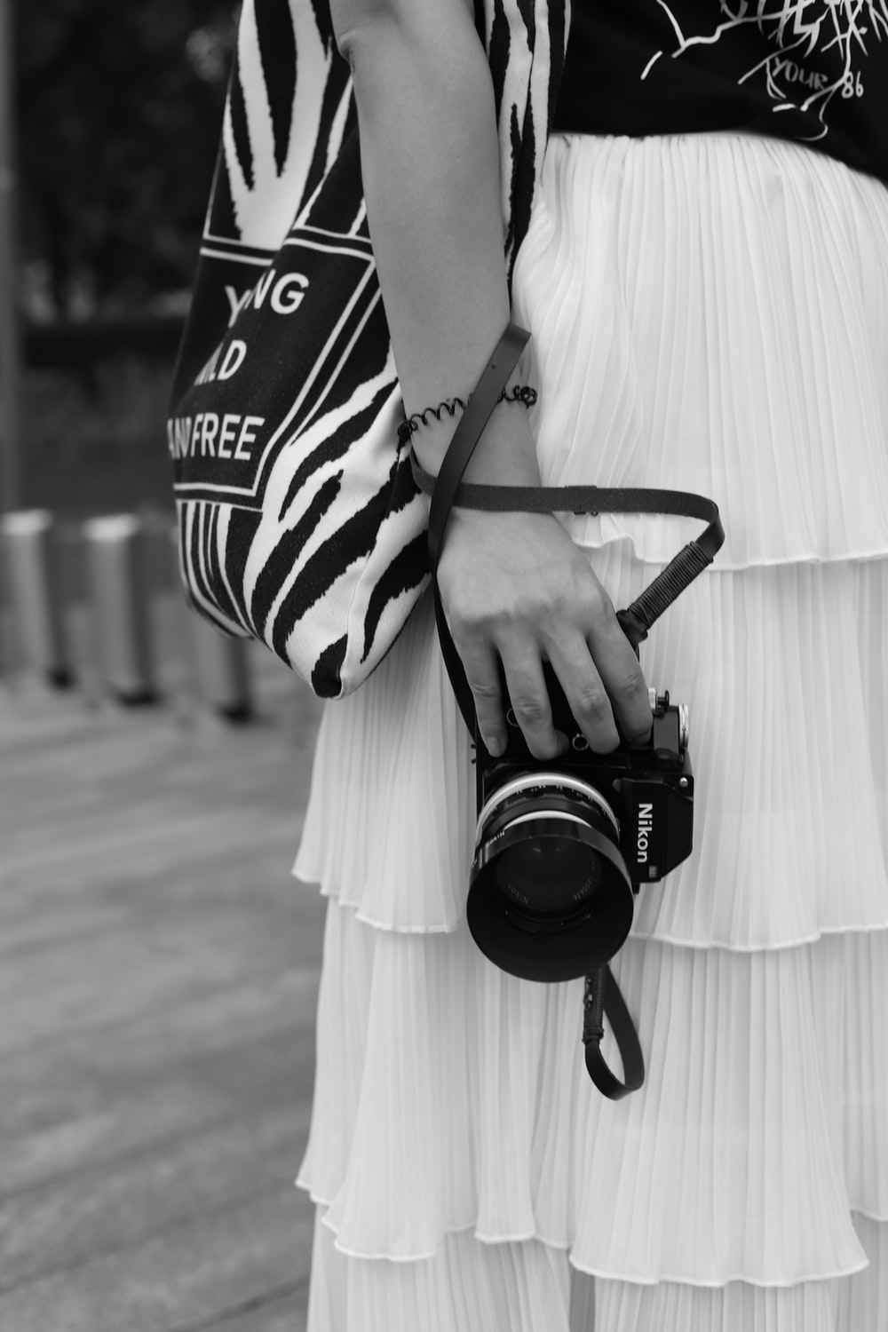 grayscale photo of woman wearing skirt and blouse holding DSLR camera