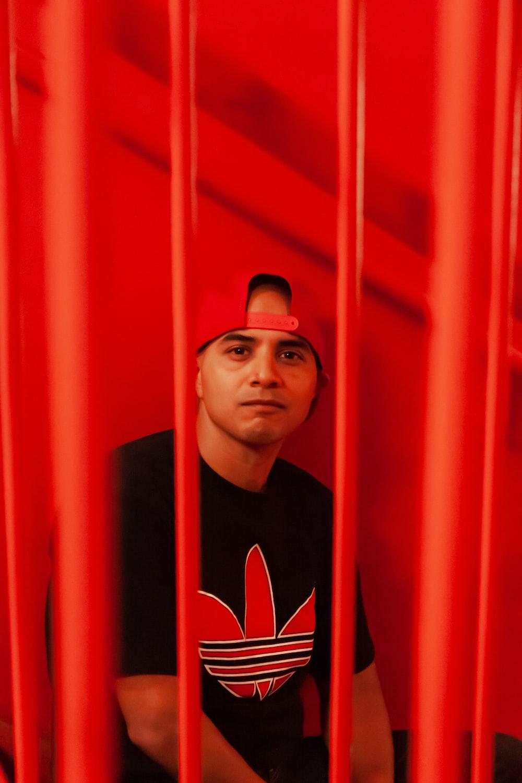 man wearing black and red Adidas shirt and red baseball cap