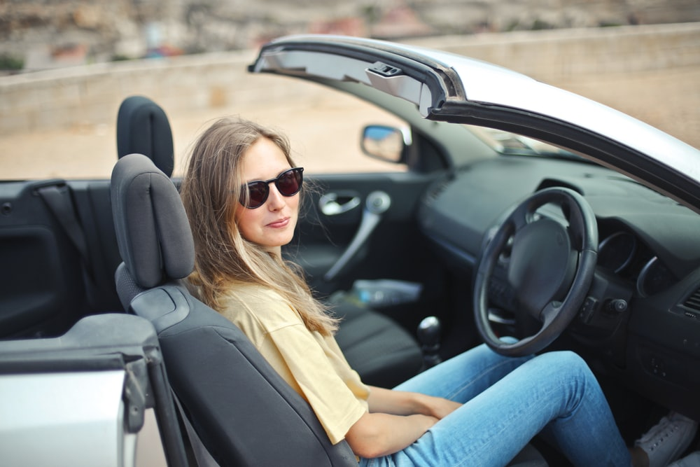 smiling woman sitting on black and white vehicle
