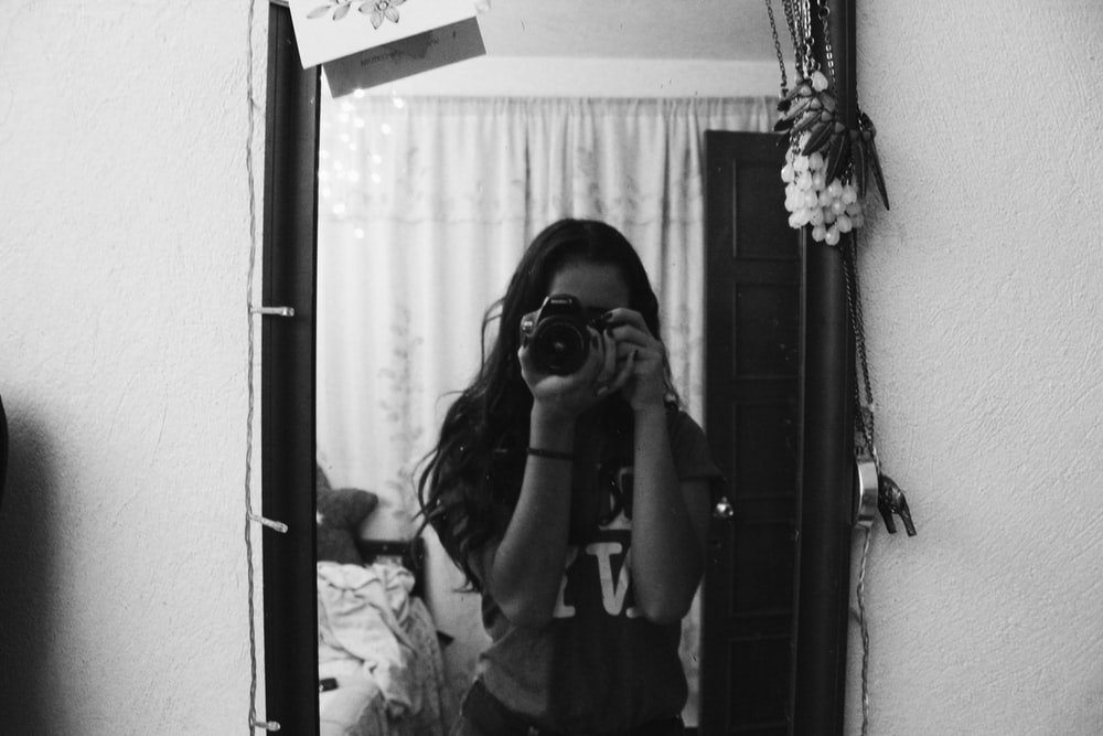 grayscale photo of woman holding camera