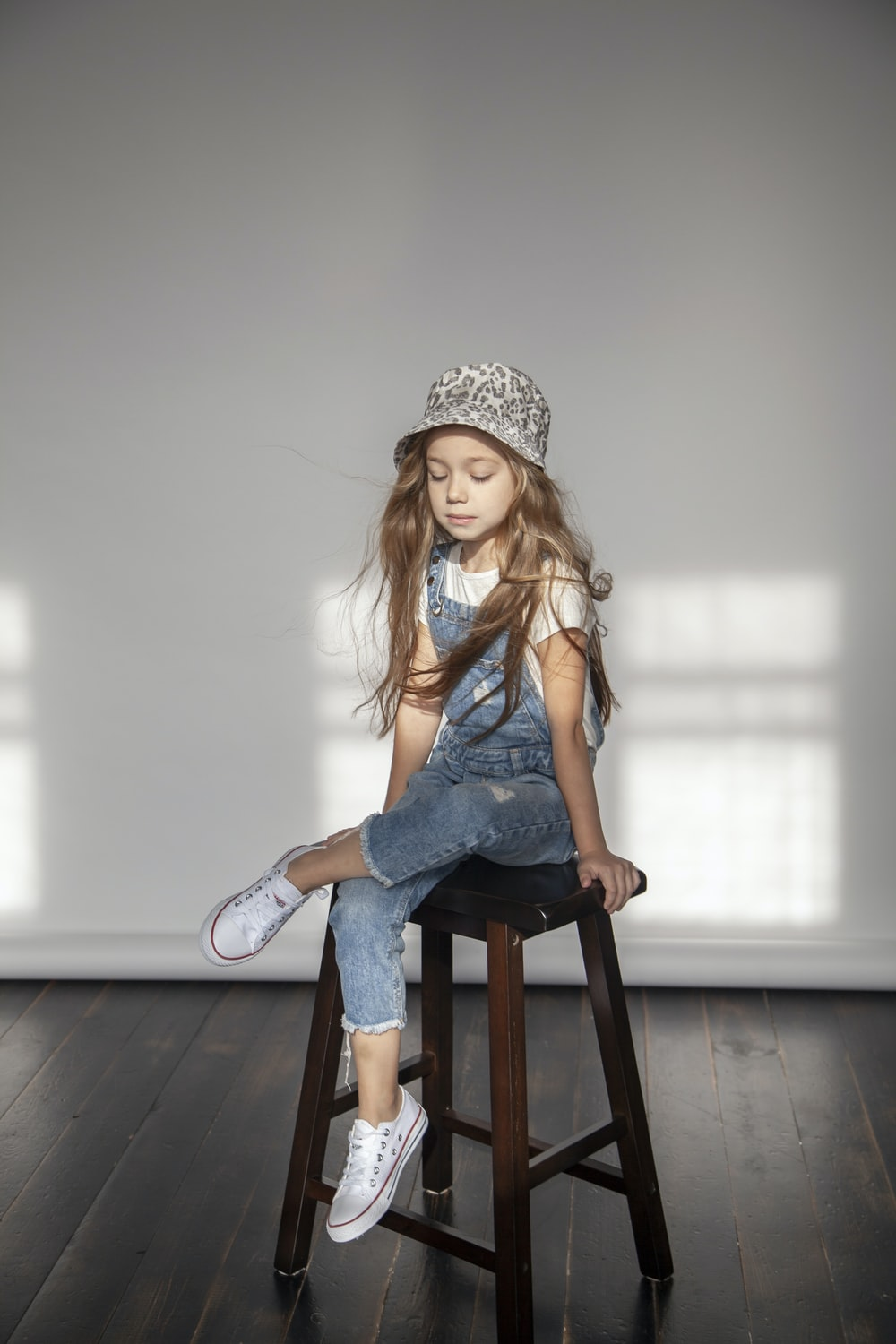 girl in blue overalls sitting on wooden stool