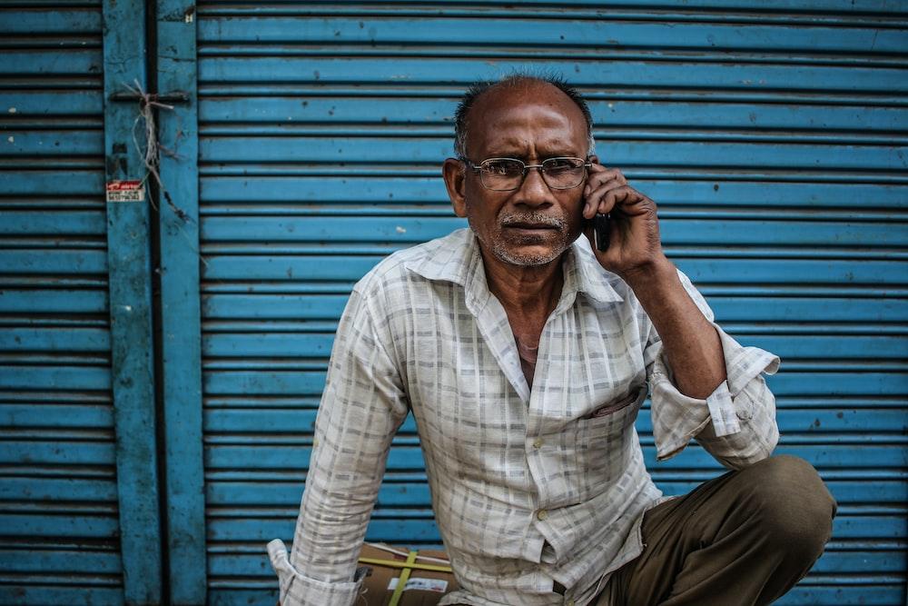 sitting man wearing gray shirt holding phone on ear