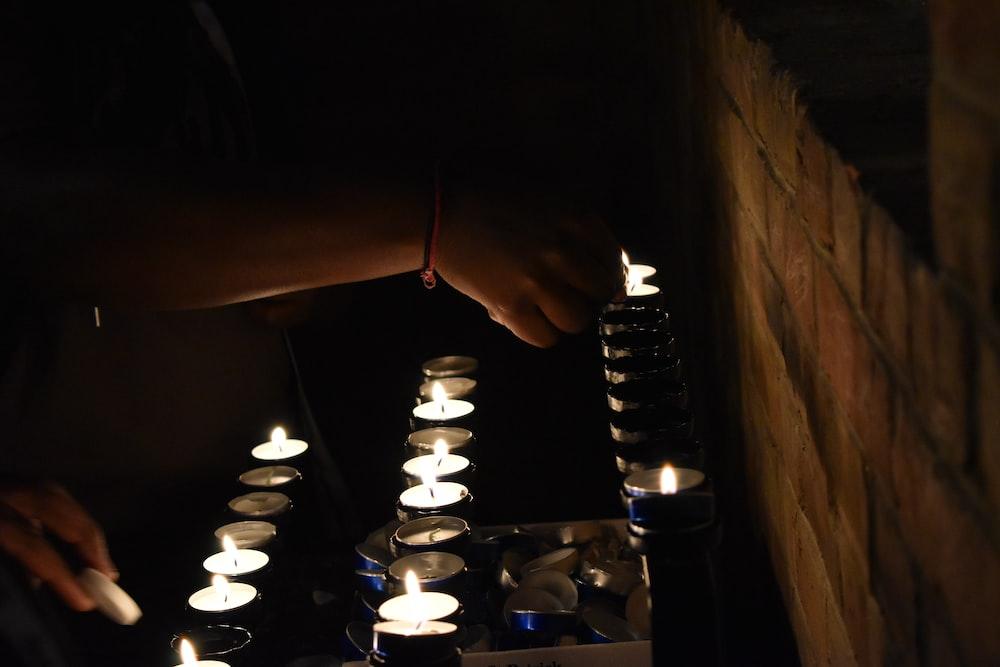 shallow focus photography of lit votive candles