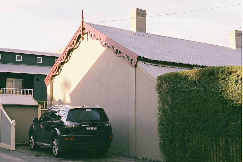 black 5-door hatchback parked besides white house