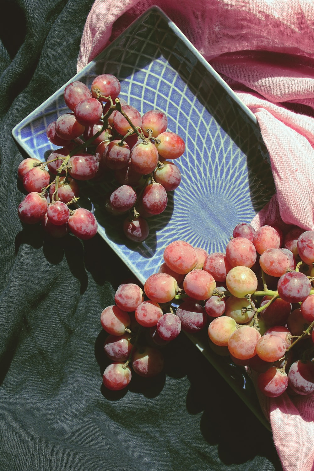red grapes in plate on textile