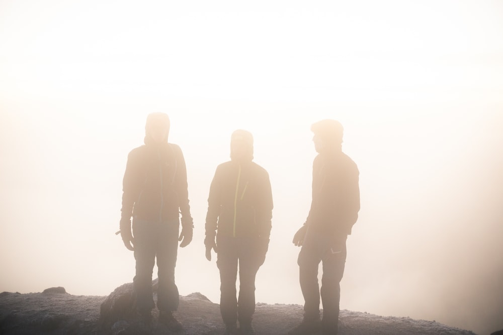 silhouette of three man on hill