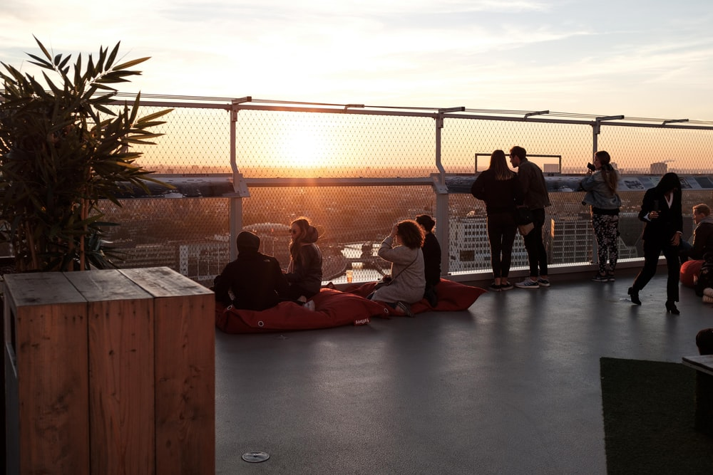 people gathering on rooftop during sunrise
