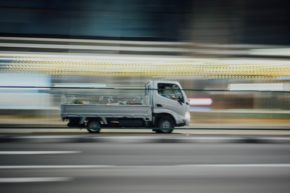 time lapse photography of drop side truck running on road