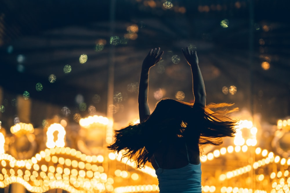 silhouette of woman raising both hands