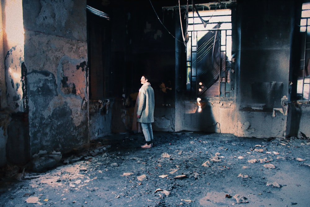man standing inside burned room
