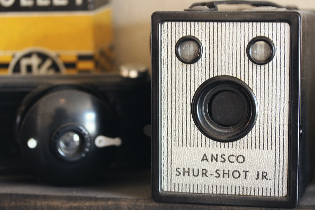 Ansco Shur-Shot Jr. vintage box camera sits on a wooden shelf, highly collectible object for photographers and other vintage camera collectors.