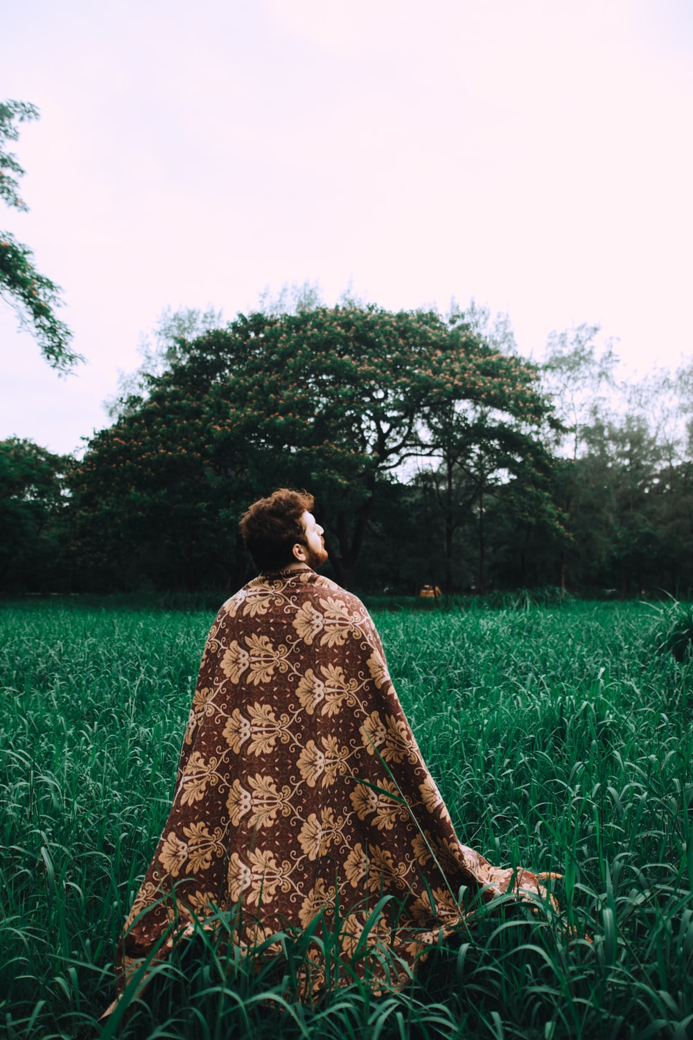 man wearing brown floral robe surrounded by grass