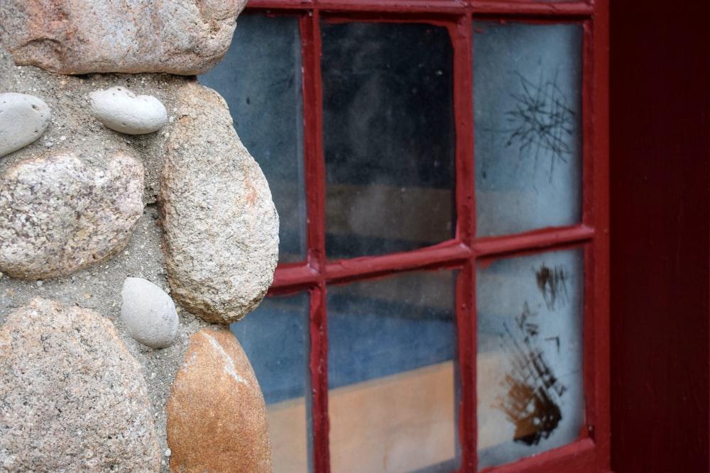 brown stones besides red metal window frame