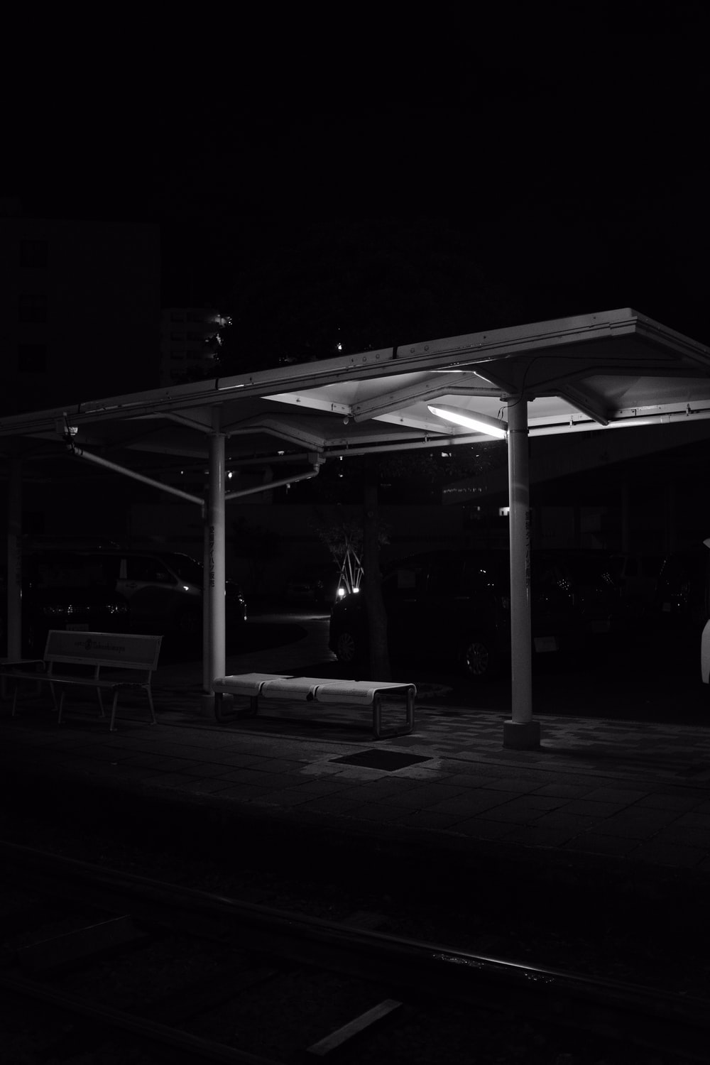 grayscale waiting shed during night