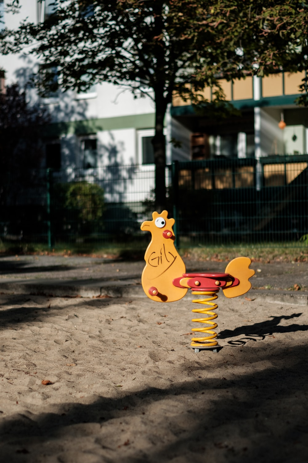 yellow and red metal chicken toy with coil spring