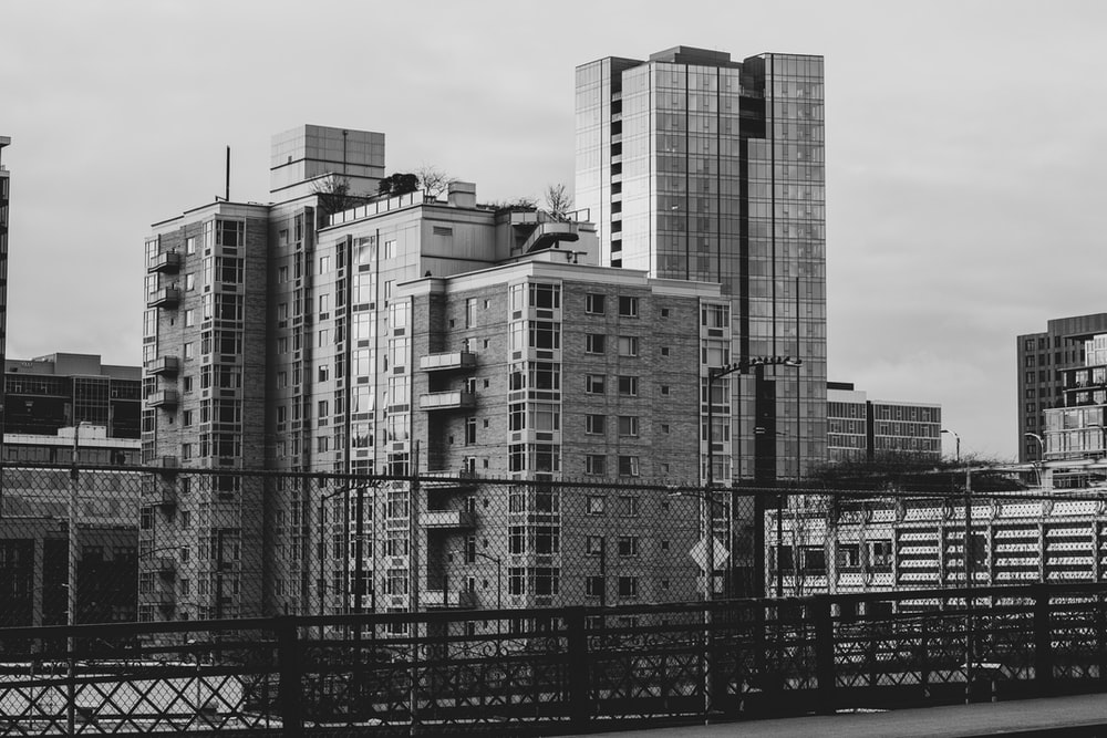 grayscale photography of high rise buildings near fence