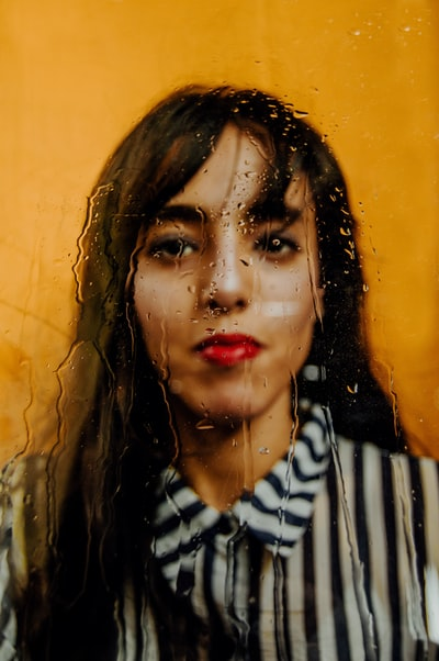 Fine Art portrait of a young model shot from behind a wet glass.