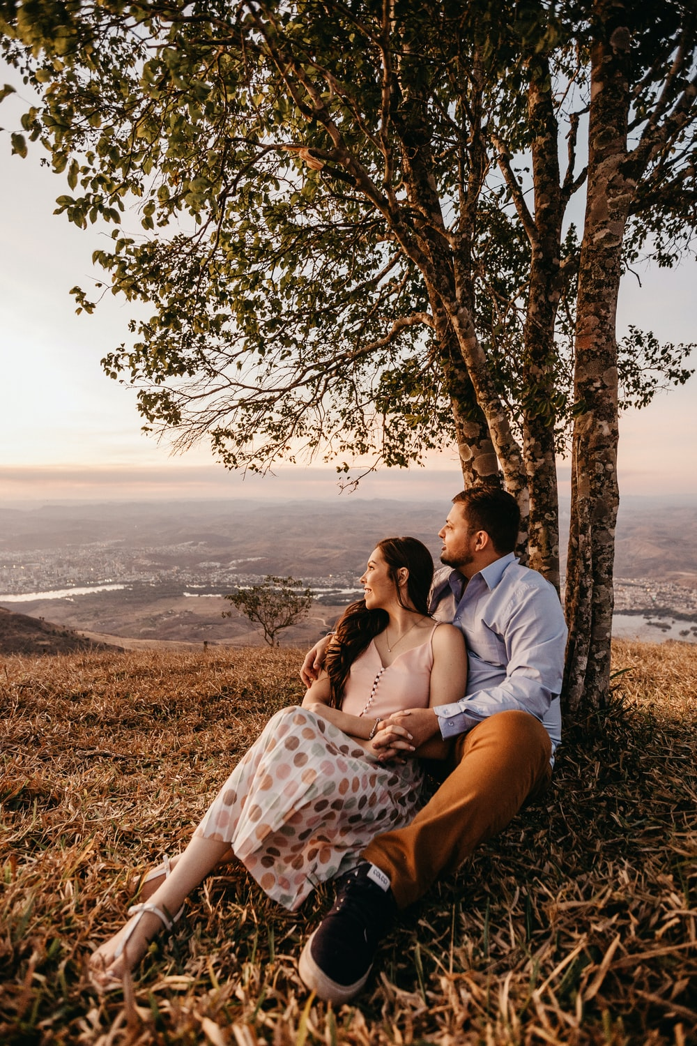 man and woman sitting beside trees