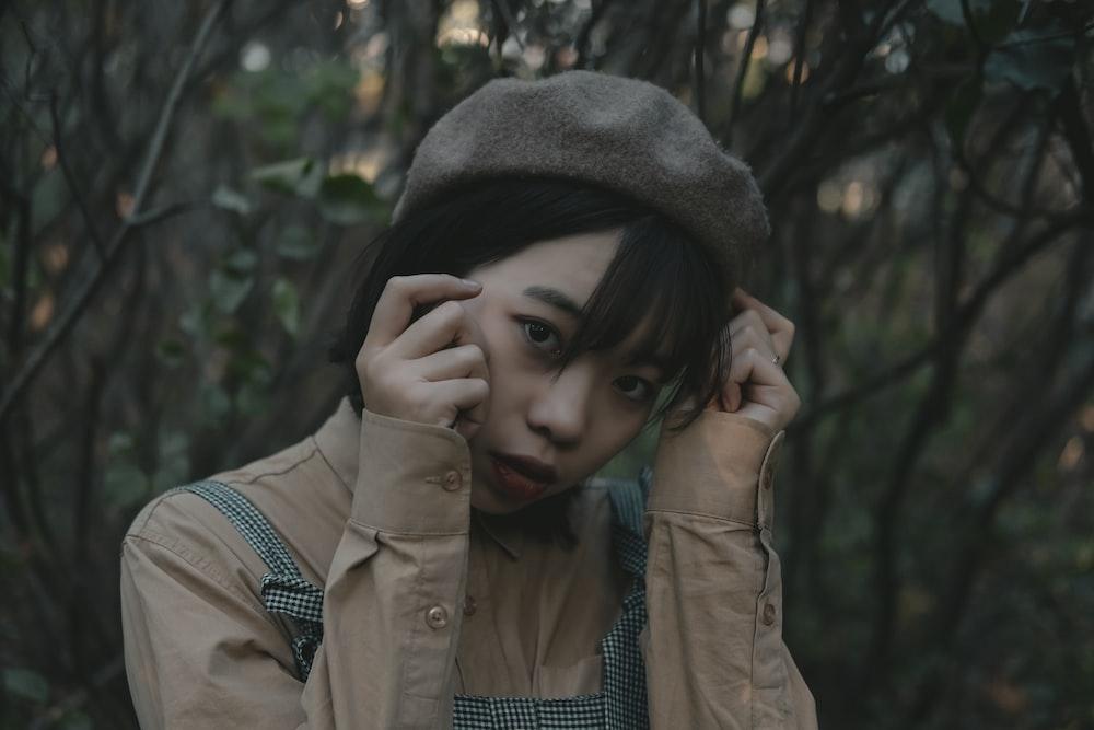 woman wearing brown dress shirt and brown cap