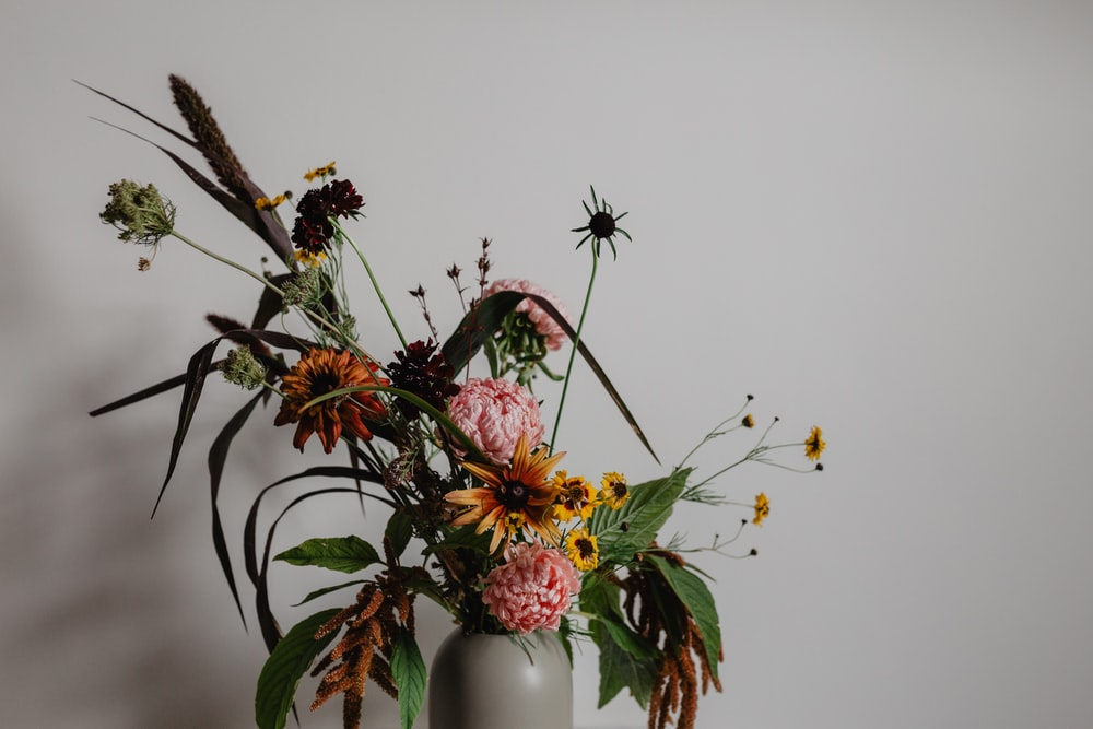 assorted flowers in vase beside wall