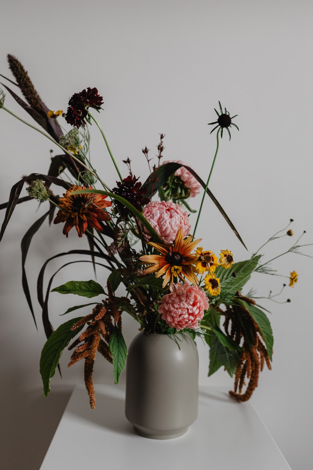 yellow and pink flowers in grey vase on white surface