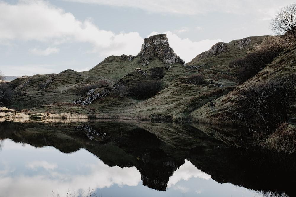 green mountain slope and lake