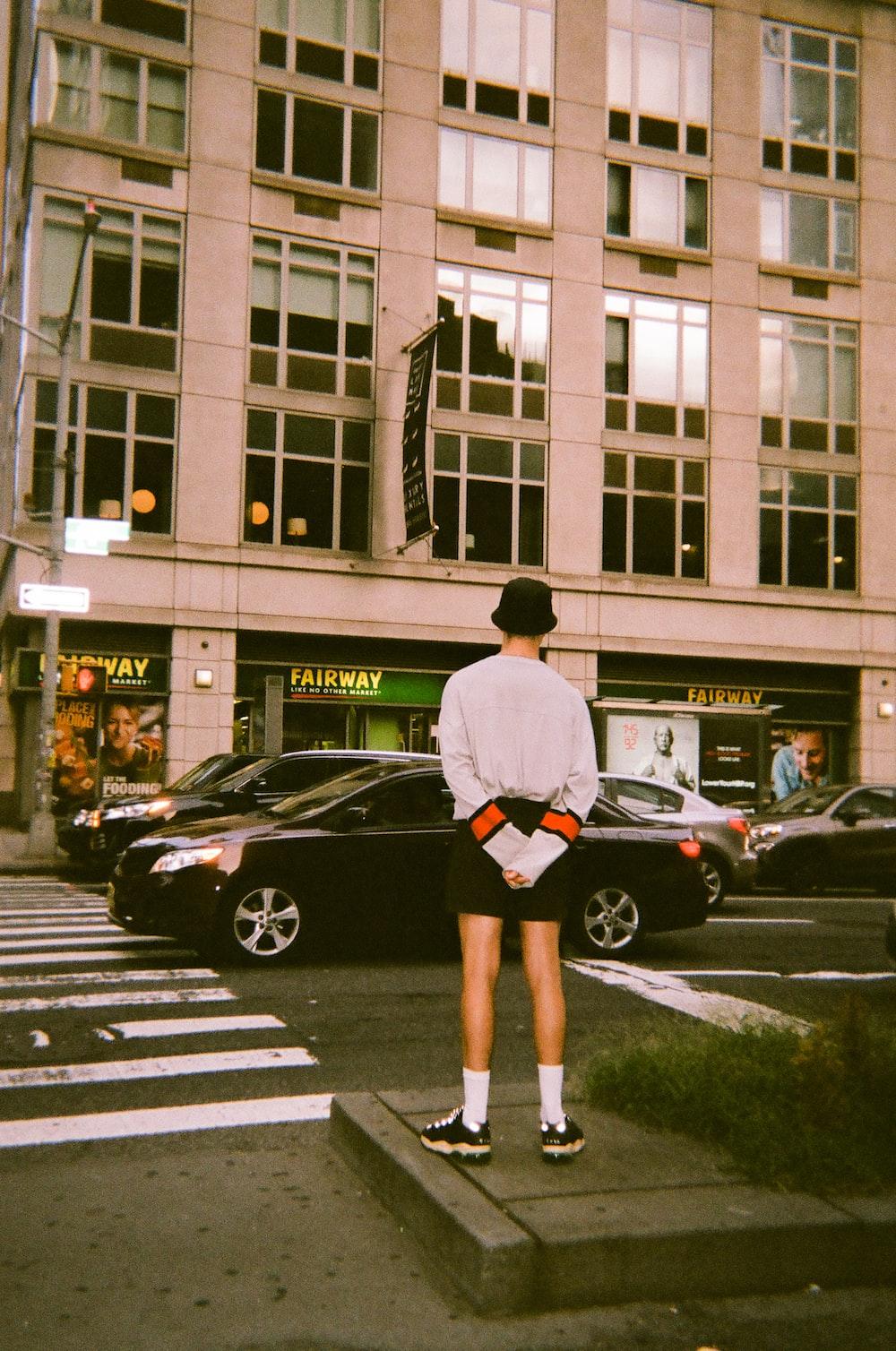 man wearing white sweater standing on sidewalk